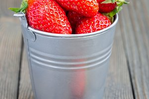 Bucket full of strawberries on a wooden background, vertical