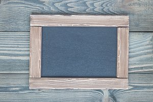 Black empty chalkboard on wooden table for copy space, horizontal, top view