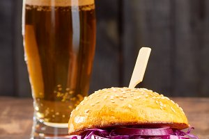 Sandwich with pulled pork and glass of beer on wooden background