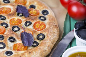 Italian focaccia with tomatoes, black olives and basil