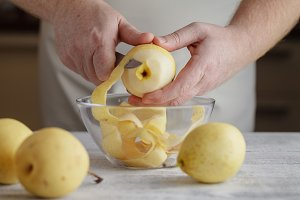 Man's hands peel pear