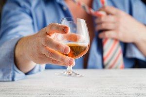 Hands with glass of cognac