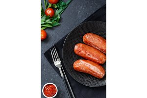 Top view on fried sausages on a black plate on a black table with tomatoes and greens.