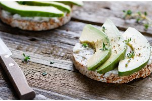 Close up of two toasts of grain bread with soft white cheese and chopped fresh avocado on old wooden gray boards .