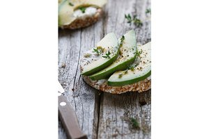 Close up of a toast of grain bread with soft white cheese and chopped fresh avocado on old wooden gray boards .