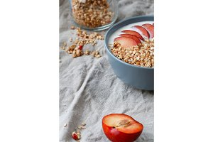 Close-up on a blue bowl with breakfast with oat flakes, yogurt and pieces of red plum on table. Copy space.