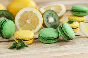 Green and yellow french macarons with kiwi, lemon and mint decorations