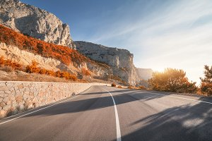 Asphalt road in mountains at sunrise in autumn