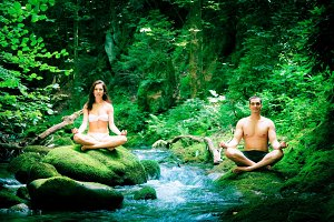 Couple Doing Yoga By The River