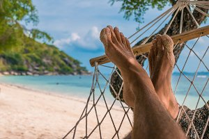 Men feet in Hammock, relaxing on the beach in Haad Rin, Ko Phangan