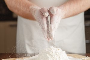 Man in apron making dough