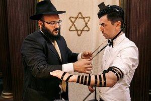 Black ribbons around groom's hands