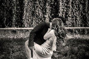 Man holds woman's leg in a garden