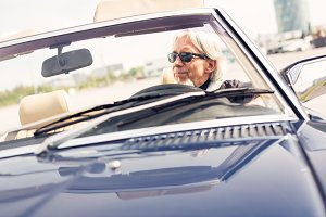 Senior Man Driving A Convertible Classic Car