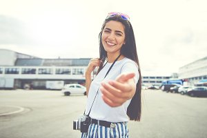 Cute young woman holding out her hand
