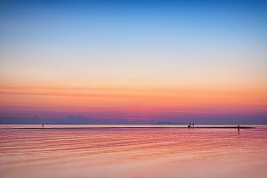 Beautiful calm sunset with people walking on sand spit