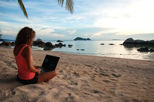 Lady freelancer with a laptop on the beach on the sunset