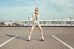 Beautiful teenage girl rollerskating in city