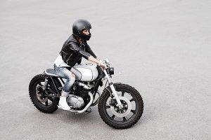 Biker woman in leather jacket on motorcycle