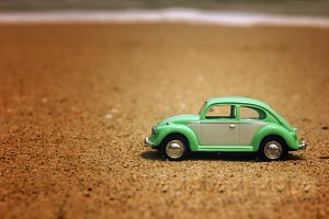 green toy car on the beach