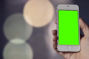 Smartphone with Green Screen on before Bokeh Background
