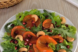 Salad greens with persimmon, pomegra