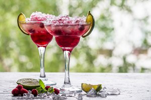 margarita cocktail with lime and raspberries