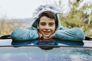 portrait of a boy disguised as a car sticking out