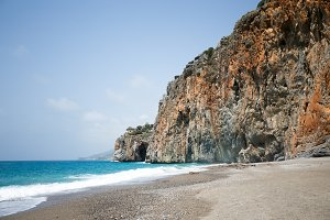 Mediterranean beach with turqouise sea and rocks on shore