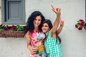 Two women with beverages doing victory sign