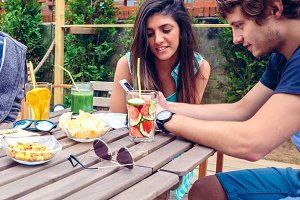 Young happy couple looking smartphone outdoors in summer