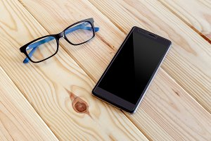 Smartphone and glasses on wooden