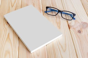 Empty book cover and glasses on wood