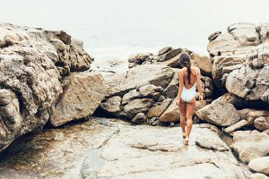 girl walking on rocks by ocean