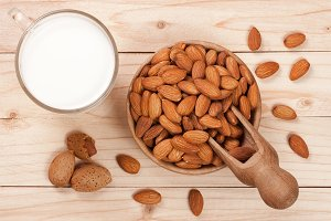 Almond milk in a glass and almonds in a bowl on light wooden background. Top view