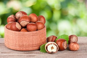 Hazelnuts with leaves in a wooden bowl on a wooden table with blurred garden background
