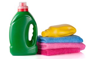 bottle laundry detergent and conditioner or fabric softener with towels isolated on white background