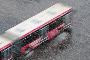Motion blur - The city bus is moving along the street during a snowfall in May. Moscow, Russia.