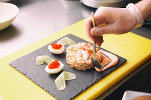 Chef is decorating crab salad