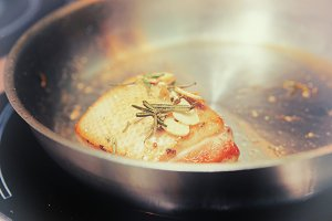 Duck fillet being fried in pan