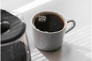 Cup of black coffee on a white table under the sunlight of the morning