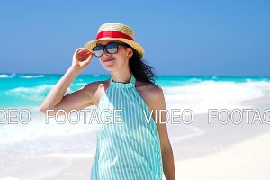 Beautiful woman smiling happy on summer holidays on white beach. Happy girl walking in summer dress. SLOW MOTION