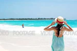 Beautiful young woman on summer holidays on white beach.Happy girl walking in summer dress in slow motion