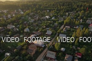 Flying over summer houses in green woods, Russia