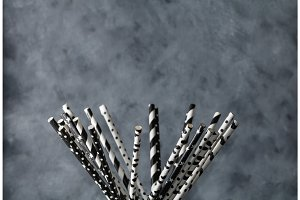A lot of black and white straws for juice on a gray-blue background.