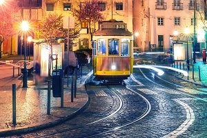 Yellow 28 tram in Alfama at night, Lisbon, Portugal