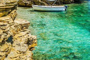 White boat in small cute azure bay surrounded by lime stone cliffs in Corfu island, Greece