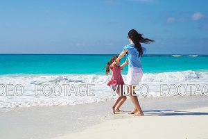 Little adorable girl and young mother at tropical beach. Family of two have a lot of fun during summer vacation