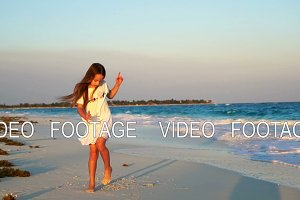 Adorable happy little girl on white beach at sunset. Cute kid dance on the tropical seashore in slow motion video
