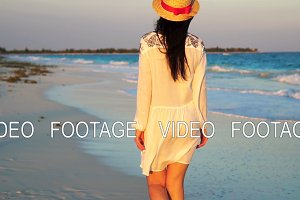 Beautiful woman on summer holidays on white beach. Happy girl walking in summer dress. SLOW MOTION